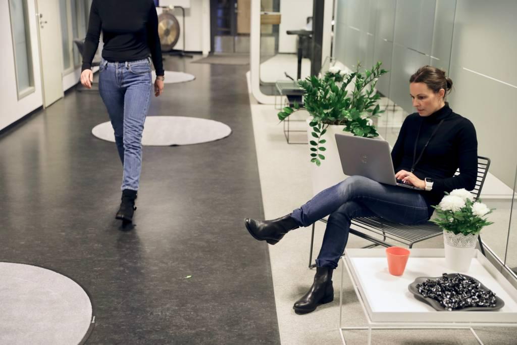 Elmon toimiston käytävä, nainen istuu tietokoneen kanssa ja toinen kävelee ohi