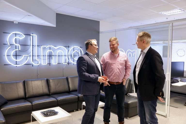 Kolme ihmistä keskustelemassa Elmon toimistolla