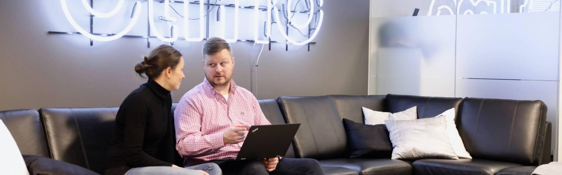 Kaksi Elmon työntekijää istuvat Elmon toimiston sohvalla