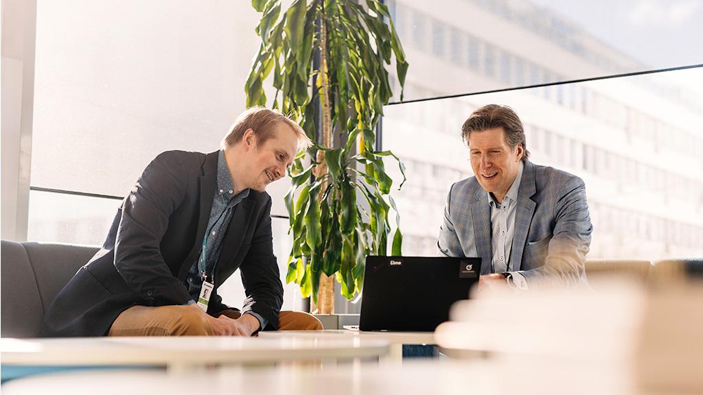 Kaksi miestä katsovat tietokoneen näyttöä