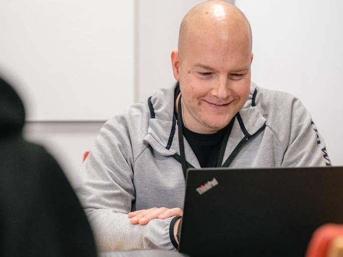 Mies hymyilee ja käyttää kannettavaa tietokonetta